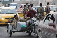 Personas conduciendo una motocicleta pertenenciente a la armada iraquí en un punto de quiebre en Kurdish, en las afueras de Kirkuk, 11 de junio de 2014. El crudo Brent recortaba sus ganancias el viernes, aunque se mantenía por encima de 113 dólares el barril, ante un alivio en las preocupaciones de que la insurgencia en Irak pueda provocar una interrupción repentina y significativa en las exportaciones petroleras del país. REUTERS/Ako Rasheed
