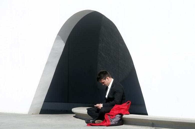 A man uses his mobile phone near the entrance to Mobile World Congress in Barcelona February 22, 2014.  REUTERS/Albert Gea/Files