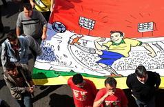 Manifestantes, que foram barrados por um cordão de isolamento antes de chegar ao estádio Mané Garrincha, marcham rumo a estádio para protestar contra os gastos com a Copa do Mundo. 15/6/2014.  REUTERS/Joedson Alves