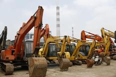 Экскаваторы на фоне труб угольной ТЭС в Шанхае 5 июня 2014 года.  Китай уверен, что достигнет ориентира роста в 7,5 процента в этом году, заявил премьер-министр Ли Кэцян в понедельник, добавив, что правительство готово скорректировать политику, чтобы гарантировать такой результат. REUTERS/Aly Song