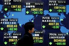 Una mujer camina frente a una pantalla electrónica que muestra el Nikkei japonés y varios precios de otros países, fuera de una bolsa de valores en Tokio, 4 de diciembre de 2013.  La mayoría de las bolsas de Asia se debilitaba el lunes y el petróleo extendía sus ganancias y se acercaba a máximos en nueve meses por el temor a que la insurgencia en Irak pueda extenderse e interrumpir las exportaciones de crudo. REUTERS/Toru Hanai