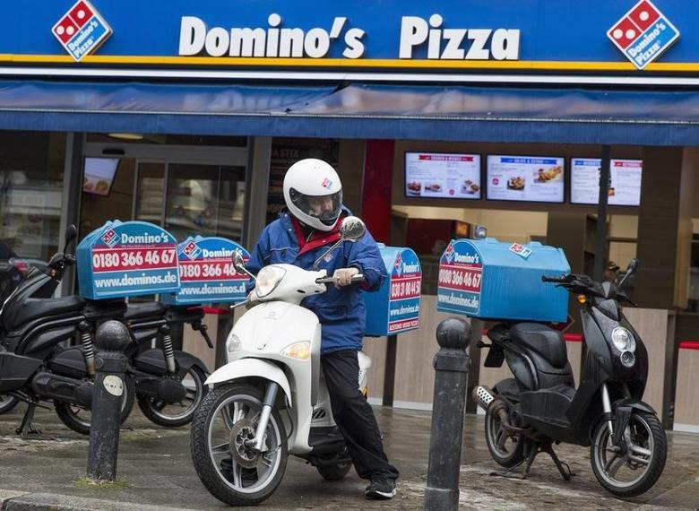 A staff member delivers take-away pizzas to customers at a Domino's Pizza store in Berlin, August 19, 2013. REUTERS/Thomas Peter/Files
