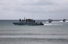Суда ВМС Малайзии у берега острова Борнео 20 февраля 2013 года. Переполненная деревянная лодка, предположительно перевозившая 97 нелегальных мигрантов из Индонезии, затонула у западного побережья Малайзии. Спасатели ищут 42 человек, пропавших без вести, сообщили малайзийские власти. REUTERS/Bazuki Muhammad