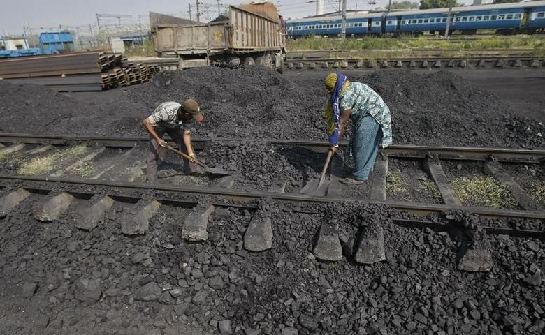 Workers clear a track in a railway coal yard on the outskirts of Ahmedabad November 25, 2013. REUTERS/Amit Dave/Files