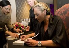 "Nelson Mandela's former private assistant Zelda la Grange signs a copy of her book ""Good Morning, Mr Mandela"" at the book launch in Johannesburg, June 19, 2014. REUTERS/Rogan Ward"
