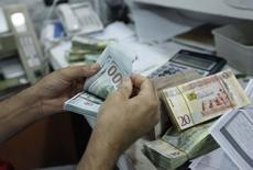 Un hombre cuenta dólares americanos en una oficina de una casa de cambio en Tripoli, 3 de junio de 2014. El dólar subía el viernes ante el alza de los rendimientos de los bonos del Tesoro estadounidense, mientras que la libra esterlina salía de recientes máximos ante las expectativas de que el Banco de Inglaterra eleve las tasas de interés a inicios del 2015 ante señales de fortalecimiento de la economía local.  REUTERS/Ismail Zitouny
