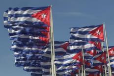 Imagen de archivo de unas banderas de Cuba frente al edificio de la Sección de Intereses de los Estados Unidos en La Habana, 31 de diciembre de 2013. El crecimiento de Cuba se desaceleró en el primer semestre de 2014 a pesar de las reformas económicas iniciadas por presidente Raúl Castro, lo que llevó al Gobierno a reducir su previsión de crecimiento para este año a un 1,4 por ciento desde un 2,2 por ciento, informaron el lunes medios oficiales. REUTERS/Enrique de la Osa