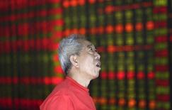 Инвестор смотрит на информационное табло в брокерской конторе в Шанхае 16 августа 2013 года. Азиатские фондовые рынки выросли во вторник благодаря улучшению макроэкономической статистики и отдельным отраслям. REUTERS/Stringer