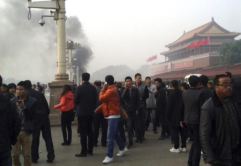 People walk along the sidewalk of Chang'an Avenue as smoke raises in front of the main entrance of the Forbidden City at Tiananmen Square in Beijing October 28, 2013. REUTERS/Stringer