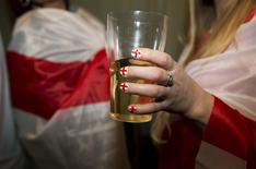 A England soccer fan holds a glass with her nails painted in her teams colours as she watches her team play against Italy during the 2014 World Cup at a bar in central London June 14, 2014. REUTERS/Neil Hall