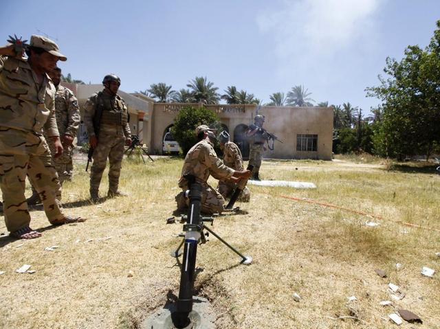 Members of the Iraqi security forces fire a mortar during clashes with fighters from Sunni militant group Islamic State of Iraq and the Levant (ISIL) in Ibrahim bin Ali village, west of Baghdad, June 24, 2014.   REUTERS/Ahmed Saad