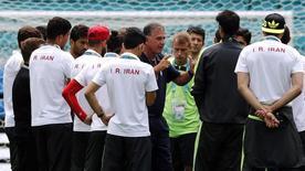 Тренер сборной Ирана Карлуш Кейруш (в центре лицом к фотографу) ведет тренировочное занятие в Салвадоре 24 июня 2014 года. Сборная Боснии и Герцеговины в среду сыграет с командой Ирана в матче группы F чемпионата мира по футболу, проходящего в Бразилии. REUTERS/Marcos Brindicci