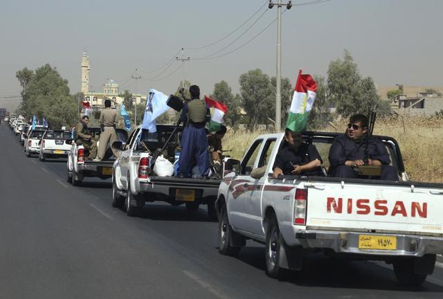 A military convoy drives towards Kirkuk, to reinforce Kurdish Peshmerga troops in Kirkuk, in this photograph taken through a window June 24, 2014. REUTERS/Yahya Ahmad