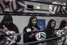 Trabalhadoras muçulmanas realizam checagem final de produtos em fábrica de bolas para a Copa do Mundo na província de Punjab, Paquistão. 16/5/2014 REUTERS/Sara Farid