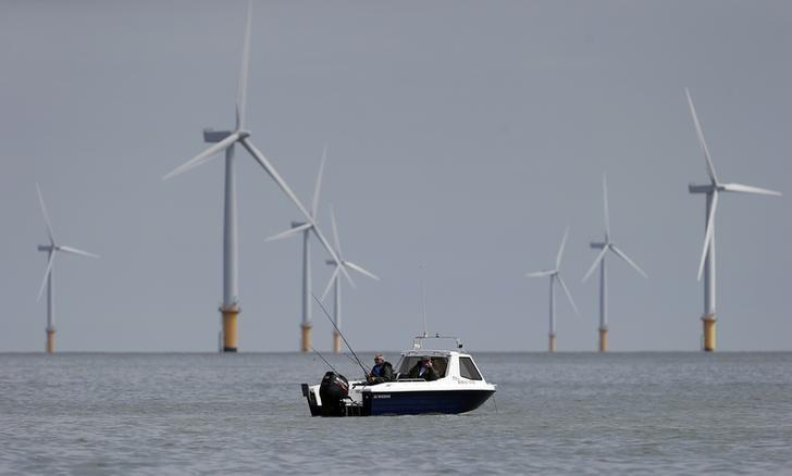Two fishermen sit in their boat at the Gunfleet Sands Offshore Wind Farm near Clacton-on-Sea in southeast England May 16, 2014. REUTERS/Suzanne Plunkett