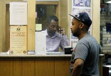 Mohammed Ahamed (R) waits as Shakir Hussein, owner of money transfer business Mustaqbal Express in Minneapolis, wires money to his ex-wife in Somalia, June 23, 2014.  REUTERS/Eric Miller