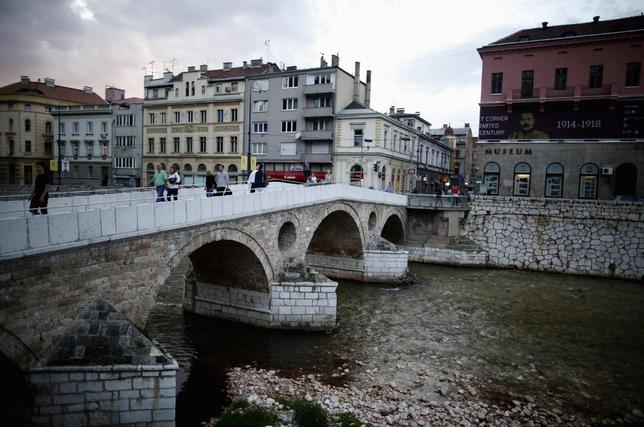 People cross the Latin Bridge and street corner in front of the historical landmark, where Archduke Franz Ferdinand and his wife Sophie were assassinated, in Sarajevo June 24, 2014. REUTERS/Dado Ruvic