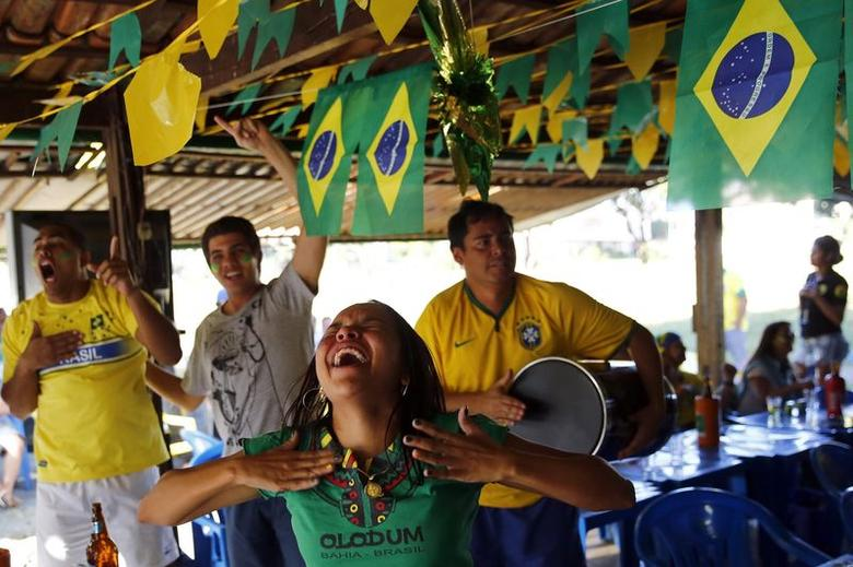 Brazil soccer fans react as they watch their team's victory against Chile during a 2014 World Cup round of 16 game, in a bar in Brasilia June 28, 2014. REUTERS/Jorge Silva