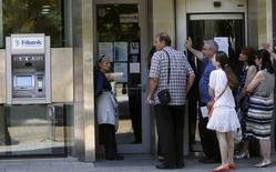Devant la First Investment Bank à Sofia, lundi. La crise bancaire semblait s'atténuer en Bulgarie après l'assurance apportée par les autorités aux déposants que leurs économies étaient en sécurité et le feu vert donné par la Commission européenne à l'octroi d'une aide gouvernementale aux établissements en difficulté. /Photo prise le 30 juin 2014/REUTERS/Stoyan Nenov