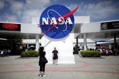 En la imagen, unos turistas toman fotos de un cartel de la NASA en Cabo Cañaveral, Florida, 14 de abril de 2010.  La agencia espacial de Estados Unidos (NASA) lanzó el sábado un balón de helio, que transportó una nave experimental con forma de platillo, desde una torre en una base naval en Kauai en Hawai, para probar sistemas de aterrizaje para futuras misiones a Marte. REUTERS/Carlos Barria