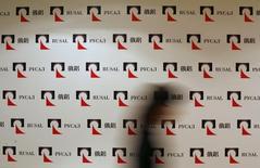 Женщина проходит мимо логотипов Русала на пресс-конференции в Гонконге 11 января 2010 года. Убыточный и сильно задолжавший алюминиевый гигант Русал получил согласие немецкого кредитора Portigon AG на рефинансирование долга в $3,6 миллиарда, сказали Рейтер осведомленные источники. REUTERS/Bobby Yip