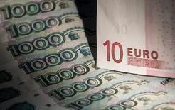 Купюры валют евро и рубль в Москве 17 февраля 2014 года. Рубль падает в первую торговую сессию июля на фоне завершения перемирия на Украине и налогового периода в РФ, что провоцирует выход из российской валюты и снижение предложения экспортной выручки на внутреннем рынке. REUTERS/Maxim Shemetov
