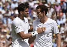 Grigor Dimitrov of Bulgaria (L) speaks to Andy Murray of Britain after defeating him in their men's singles quarter-final tennis match at the Wimbledon Tennis Championships, in London July 2, 2014. REUTERS/Toby Melville