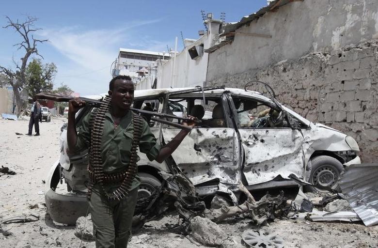 A Somali government soldier walks next to a car damaged in an explosion near Al Mukaram Hotel in Mogadishu March 15, 2014. REUTERS/Omar Faruk