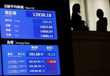Una pantalla electrónica muestra el promedio del nikkei japonés y el ranking de valores del yen japonés contra el dólar americano en la bolsa de valores en Tokio, 11 de abril de 2014. El índice Nikkei de la bolsa de Tokio subió el viernes a un máximo en cinco meses y medio después de que un reporte de empleo en Estados Unidos mucho más sólido que lo previsto aumentó la confianza de los inversores. REUTERS/Issei Kato