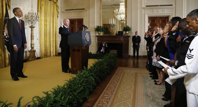 U.S. President Barack Obama (L) looks on as Deputy Secretary of Homeland Security Alejandro Mayorkas (C, at podium) administers the Oath of Allegiance to members of the U.S. military and military spouses at a ceremony for them to become naturalized U.S. citizens at the White House in Washington July 4, 2014. REUTERS/Jonathan Ernst