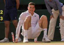 Jul 4, 2014; London, United Kingdom; Milos Raonic (CAN) falls during his match against Roger Federer (SUI) on day 11 of the 2014 Wimbledon Championships at the All England Lawn and Tennis Club. Mandatory Credit: Susan Mullane-USA TODAY Sports