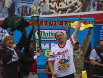 Joey Chestnut (centro) comemora após vencer o Famoso Concurso Internacional dos Devoradores de Cachorro-Quente do Quatro de Julho, da Nathan's, em Coney Island, nos EUA, nesta sexta-feira. 04/07/2014 REUTERS/Eric Thayer