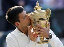 Novak Djokovic of Serbia kisses the winners trophy after defeating Roger Federer of Switzerland  in their men's singles final tennis match at the Wimbledon Tennis Championships, in London July 6, 2014.      REUTERS/Suzanne Plunkett