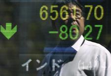 Отражение мужчины в экране брокерской конторы в Токио, 14 апреля 2014 года. Азиатские фондовые рынки, кроме Китая, снизились в понедельник под влиянием локальных факторов. REUTERS/Issei Kato
