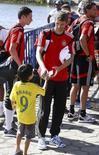 Jogador alemão Thomas Mueller (centro) assina autógrafo para garoto brasileiro em Santa Cruz Cabrália (BA). 7/7/2014 REUTERS/Arnd Wiegmann