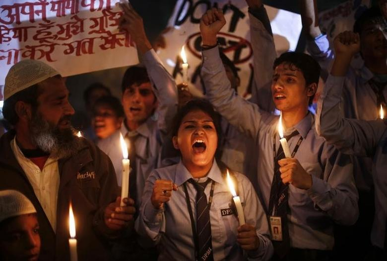 School children shout slogans as they hold candles during a candle light vigil to mark the first anniversary of the Delhi gang rape, in New Delhi December 16, 2013. REUTERS/Adnan Abidi/Files