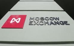 Логотип Московской биржи у входа в её офис в Москве 14 марта 2014 года. Российские фондовые индексы продолжили повышение в начале торгов вторника, и рублевый индикатор поднялся в район максимума этого года. REUTERS/Maxim Shemetov