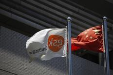 A flag (L) bearing the logo of GlaxoSmithKline (GSK) flutters next to a Chinese national flag outside a GlaxoSmithKline office building in Shanghai July 12, 2013.  REUTERS/Aly Song
