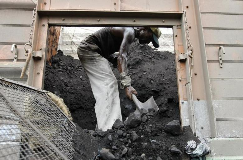 A labourer unloads coal from a supply truck at a yard on the outskirts of Ahmedabad August 21, 2013. REUTERS/Amit Dave/Files