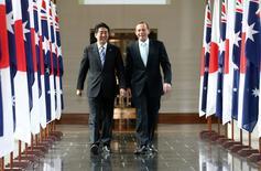 Премьер-министры Японии и Австралии Синдзо Абэ (слева) и Тони Эбботт выходят из здания парламента в Канберре 8 июля 2014 года. Премьер-министры Японии и Австралии Синдзо Абэ и Тони Эбботт подписали во вторник пакт об экономическом партнерстве, а также соглашение о поставках военного и технологического оборудования. REUTERS/Alex Ellinghausen/Pool