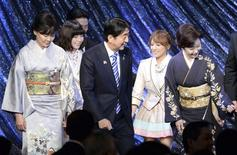 Japan's Prime Minister Shinzo Abe (C) and his wife Akie (L) are led to the stage by Japanese singer Natsuko Godai (R) and members of Japanese girls' pop group AKB48, Haruka Shimazaki (2nd L) and Minami Takahashi (2nd R), during a gala dinner of the ASEAN-Japan Commemorative Summit meeting hosted by Abe, in Tokyo December 14, 2013. REUTERS/Toshifumi Kitamura/Pool
