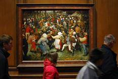 "People walks past a painting titled ""The Wedding Dance"" by artist Pieter Bruegel the Elder displayed at the Detroit Institute of Arts in Detroit, Michigan December 7, 2013. REUTERS/Joshua Lott"