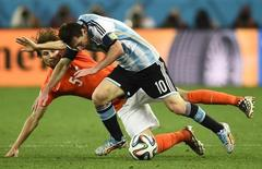 Daley Blind of the Netherlands (rear) and Argentina's Lionel Messi fight for the ball during their 2014 World Cup semi-finals at the Corinthians arena in Sao Paulo July 9, 2014. REUTERS/Dylan Martinez