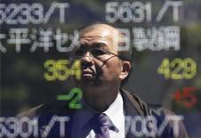 Мужчина изучает котировки на экране в Токио 14 апреля 2014 года. Азиатские фондовые рынки завершили торги четверга разнонаправленно под влиянием протокола совещания ФРС и статистики Китая. REUTERS/Issei Kato