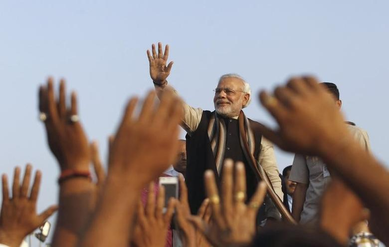 Narendra Modi waves towards supporters while flagging off vehicles with resource kits for collection of iron and soil to build ''Statue of Unity'', a 182-metre statue of Sardar Vallabhbhai Patel, in Ahmedabad December 28, 2013. REUTERS/Amit Dave/Files