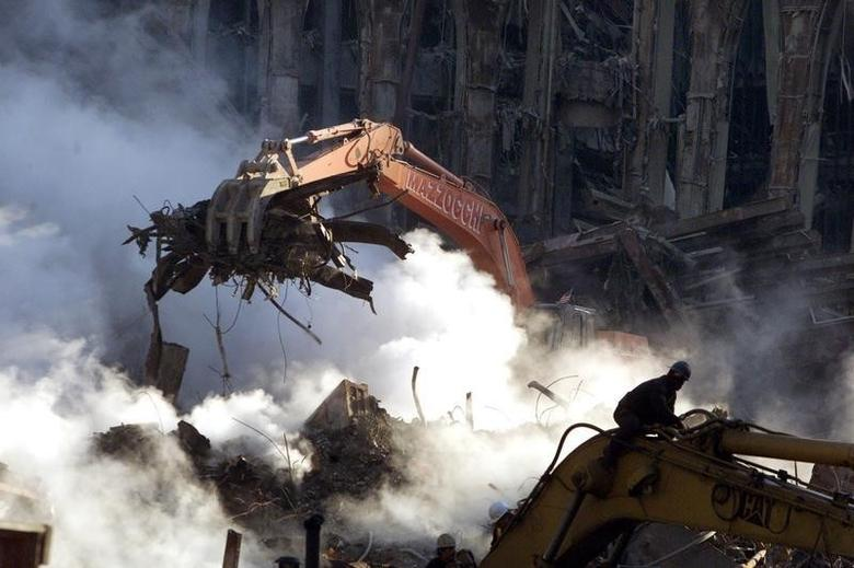 A crane lifts rubble from the ruins of the World Trade Center in New York, October 12, 2001. Smoke continues to pour from ground zero over a month after the collapse of the towers after being struck by hijackedaircraft. REUTERS/Brad Rickerby