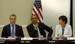 U.S. President Barack Obama holds a meeting with company executives and their small business suppliers to discuss ways to strengthen the economy at the White House in Washington July 11, 2014. Flanking Obama are National Economic Council Director Jeff Zients (L) and senior advisor Valerie Jarrett.  REUTERS/Kevin Lamarque