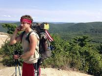 Hiker Matthew Donnelly, 30, of Milford, Pennsylvania, uses his cell phone on the Appalachian Trail in Bear Mountain, New York, July 10, 2014.   REUTERS/Barbara Goldberg