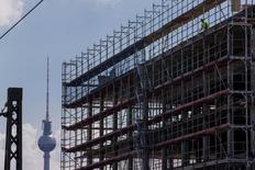 A worker is seen behind scaffoldings at a construction site near the Fernsehturm television tower in Berlin July 7, 2014. Picture taken July 7, 2014.