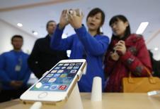 El staff de China Appla Mobil muetra y explica las nuevas funciones del iPhone5S a diferentes clientes en Beinjin, 17 de enero de 2014. Medios estatales chinos dijeron que el iPhone de Apple Inc es una amenaza para la seguridad nacional debido a la capacidad del teléfono inteligente de rastrear la ubicación de un usuario y dejar registro de la hora. REUTERS/Kim Kyung-Hoon